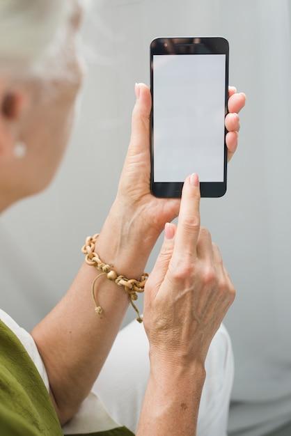 Mulher sênior tocando a tela do celular Foto gratuita