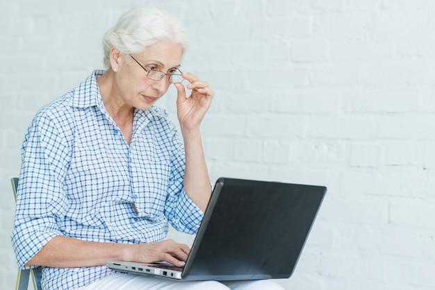 Mulher sênior usando laptop contra parede branca Foto gratuita