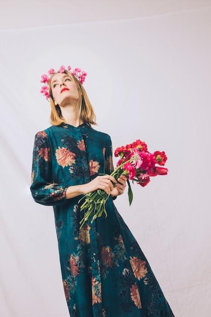 Mulher sensual atraente com coroa na cabeça e buquê de flores Foto gratuita