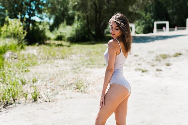 Mulher sensual em pé na praia Foto gratuita