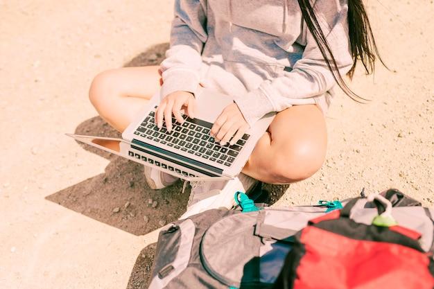 Mulher sentada com as pernas cruzadas na estrada e trabalhando no laptop Foto gratuita