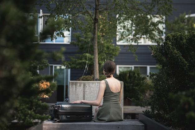 Mulher sentada com uma mala no parque Foto gratuita