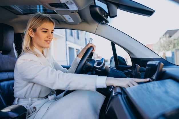 Mulher sentada dentro de carro eletro durante o carregamento Foto gratuita