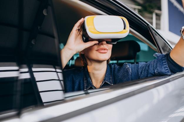 Mulher sentada dentro de um carro usando óculos vr Foto gratuita