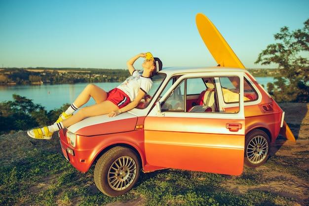 Mulher sentada e descansando no carro na praia num dia de verão perto do rio. Foto gratuita