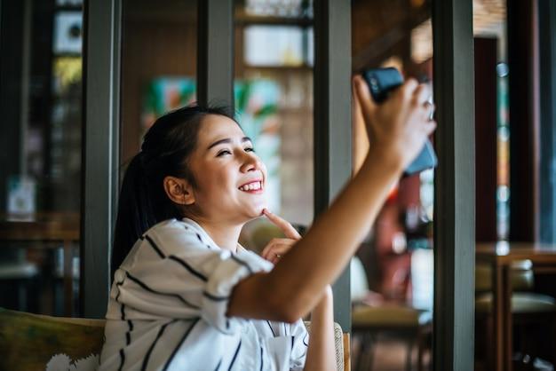 Mulher sentada e jogando seu telefone inteligente no café Foto gratuita