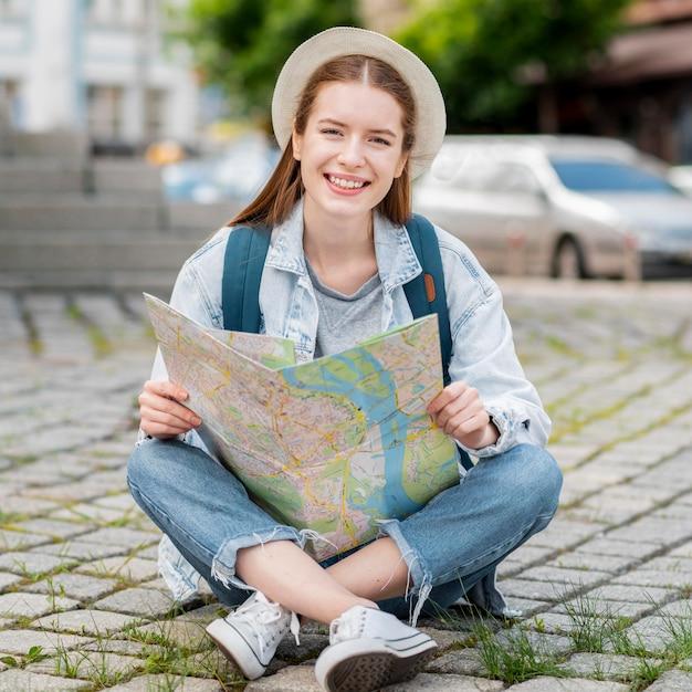 Mulher sentada e segurando um mapa Foto gratuita
