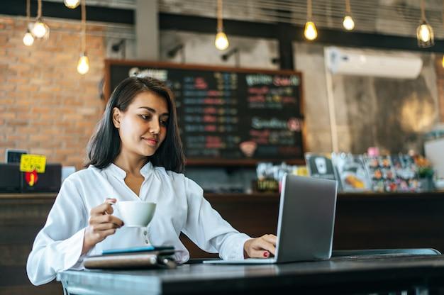 Mulher sentada e trabalhando com um laptop em uma cafeteria Foto gratuita