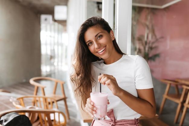 Mulher sentada em um café aconchegante mexendo seu smoothie de morango Foto gratuita