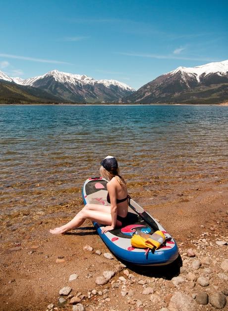 Mulher sentada em um pedal perto da água, apreciando a vista de uma montanha de neve e um céu claro Foto gratuita