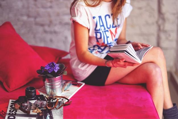 Mulher sentada em um sofá lendo uma revista Foto gratuita