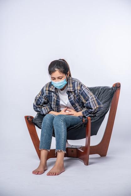 Mulher sentada em uma cadeira com dor abdominal e pressionando a mão na barriga Foto gratuita