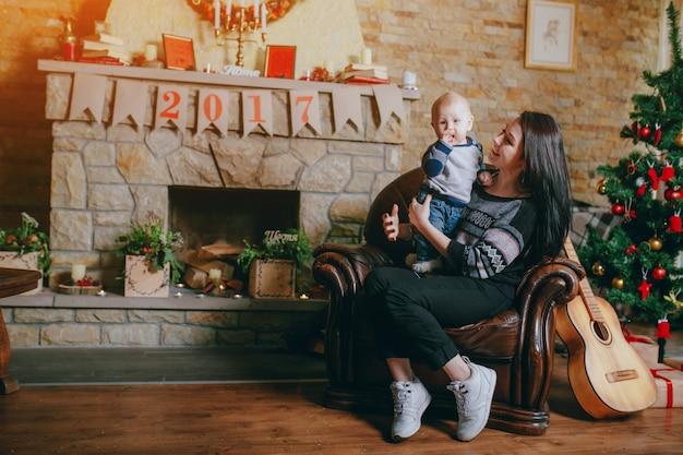 Mulher sentada em uma poltrona com seu bebê e uma guitarra ao lado e um fundo da chaminé Foto gratuita