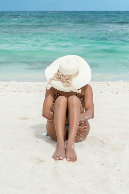 Mulher sentada na areia, abraçando as pernas dela. mulher de biquíni e chapéu na praia. inchar. mulher bronzeada bronzeamento. conceito de férias e relaxamento Foto Premium