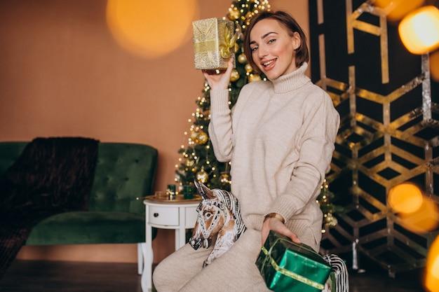 Mulher sentada na cadeira de pônei de madeira perto da árvore de natal Foto gratuita