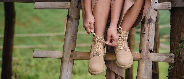 Mulher sentada na escada e usando botas Foto Premium