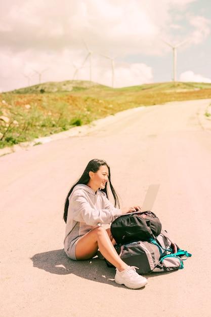 Mulher sentada na estrada e trabalhando no laptop colocado em mochilas Foto gratuita