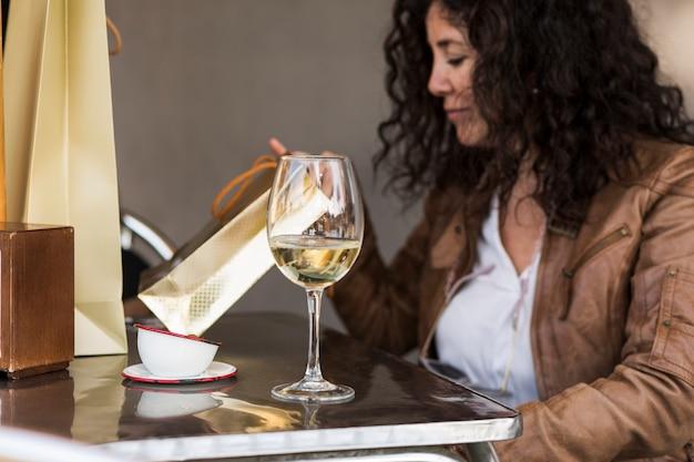 Mulher sentada na mesa com copo de vinho Foto gratuita