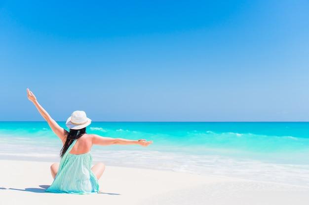Mulher sentada na praia, aproveitando as férias de verão Foto Premium