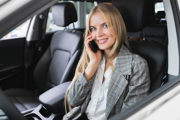 Mulher sentada no carro enquanto fala ao telefone Foto gratuita
