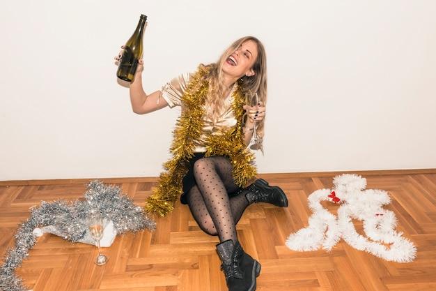 Mulher sentada no chão com garrafa de champanhe Foto gratuita