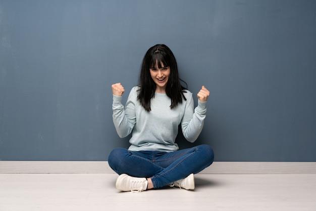 Mulher sentada no chão comemorando uma vitória na posição de vencedor Foto Premium
