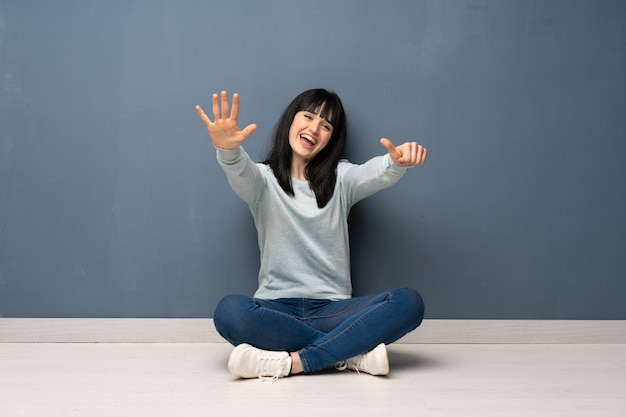 Mulher sentada no chão, contando seis com os dedos Foto Premium