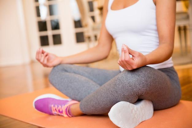 Mulher sentada no chão em casa fazendo yoga meditação Foto Premium