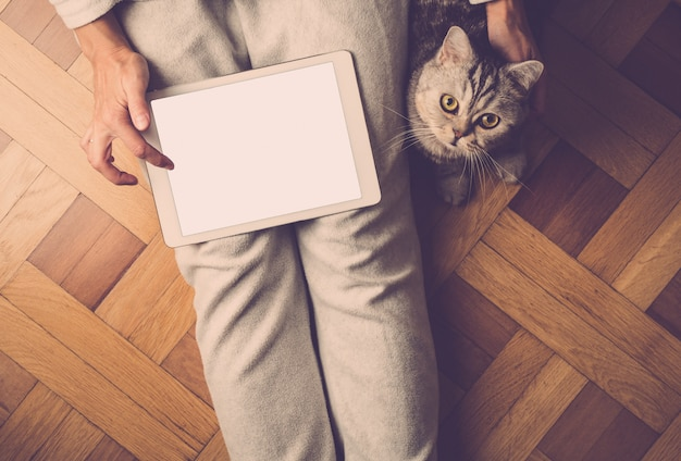 Mulher sentada no chão gato fofo e olhando para tablet, pesquisa na internet, compras on-line Foto Premium
