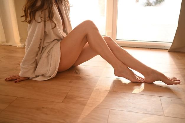 Mulher sentada no chão quente de madeira em casa dia de sol brilhante. Foto Premium
