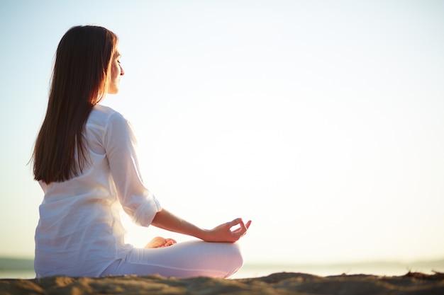 Mulher sentada no pose da ioga na praia Foto gratuita
