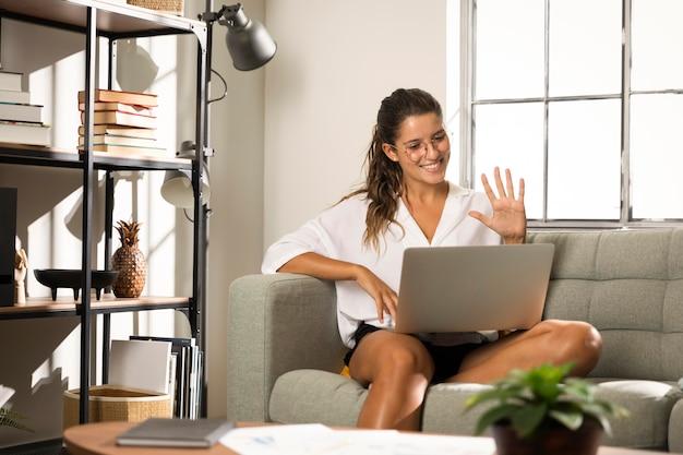 Mulher sentada no sofá com laptop Foto gratuita
