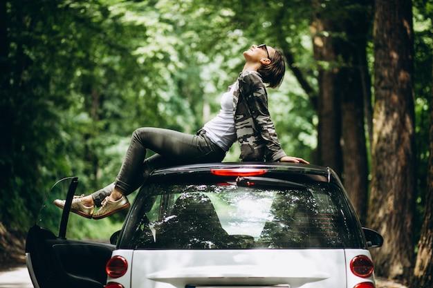 Mulher sentada no teto do carro na floresta Foto gratuita