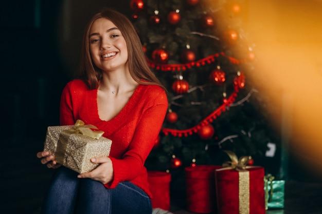 Mulher sentada perto da árvore de natal e desembalar o presente de natal Foto gratuita