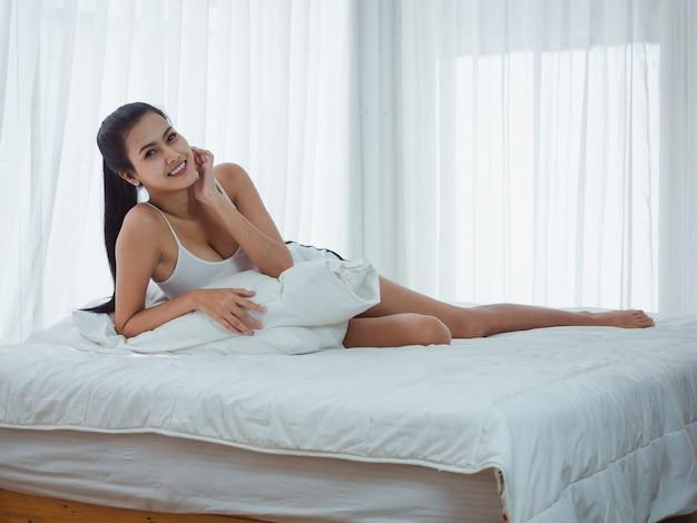Mulher sentada posa em uma cama branca, relaxar o tempo Foto Premium