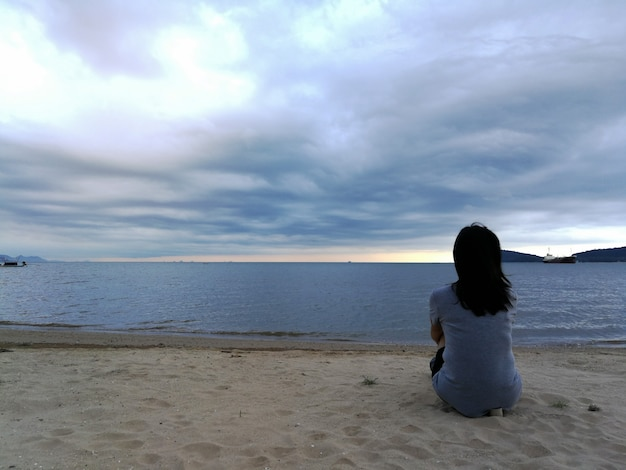 Resultado de imagem para mulher sentada na beira da praia