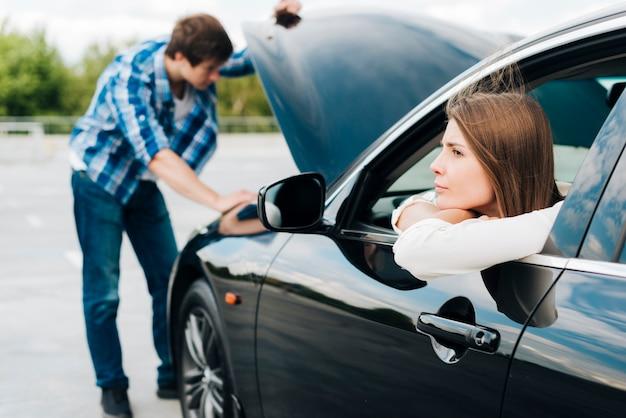 Mulher, sentando, carro, enquanto, homem, verifica, motor Foto gratuita