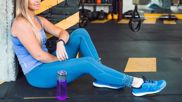 Mulher, sentando, chão, perto, garrafa água, em, ginásio Foto gratuita