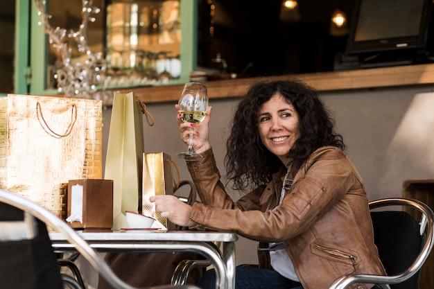 Mulher, sentando, com, bolsas para compras, e, vinho Foto gratuita