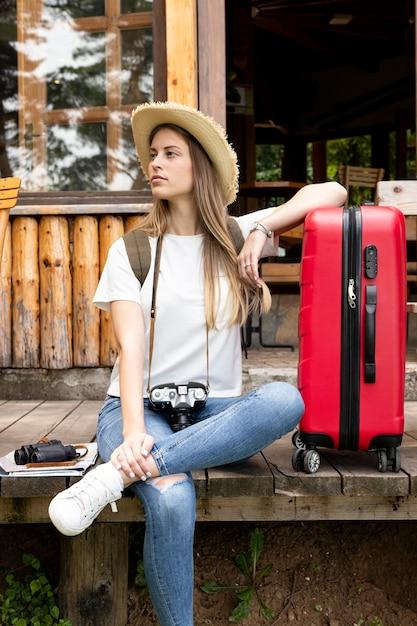 Mulher, sentando, com, dela, bagagem, e, olhando Foto gratuita