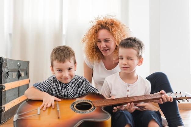 Mulher, sentando, com, dela, crianças, violão jogo Foto gratuita