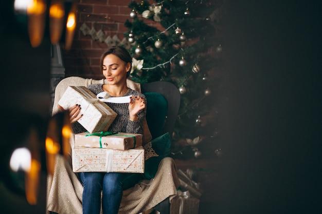 Mulher, sentando, em, cadeira, por, árvore natal Foto gratuita