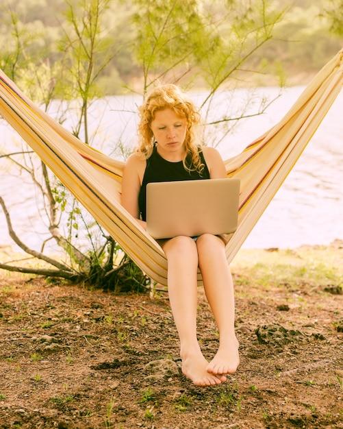 Mulher, sentando, em, rede, com, laptop Foto gratuita