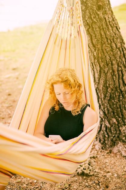 Mulher, sentando, em, rede, com, smartphone Foto gratuita
