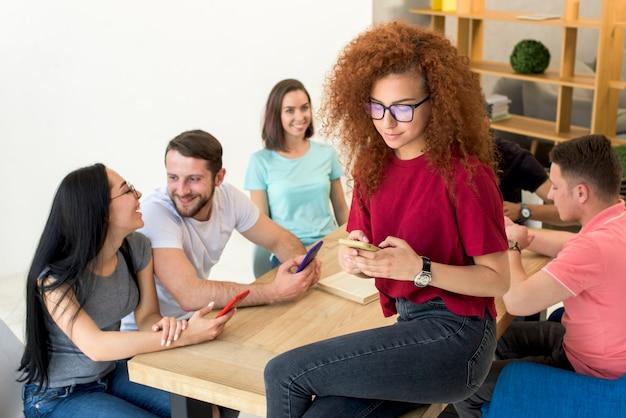 Mulher, sentando, em, tabletop, usando, telefone móvel Foto gratuita