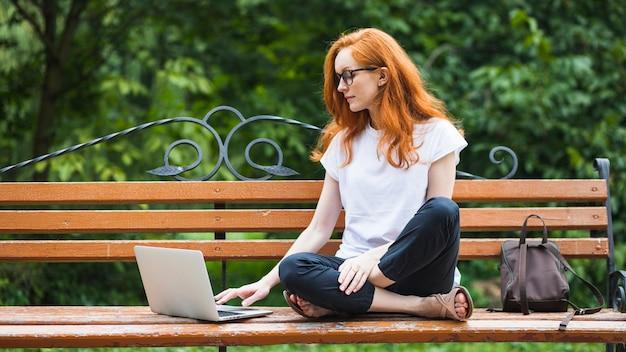 Mulher, sentando, ligado, banco, com, laptop Foto gratuita