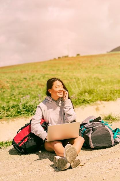 Mulher, sentando, ligado, estrada, sorrindo, e, falando telefone móvel, entre, mochilas Foto gratuita