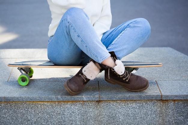 Mulher, sentando, ligado, longboard, com, pernas cruzaram Foto gratuita