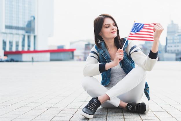 Mulher, sentando, ligado, quadrado, e, segurando, bandeira americana, em, mão Foto gratuita