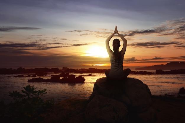 Mulher sente-se sobre a rocha fazendo yoga Foto Premium